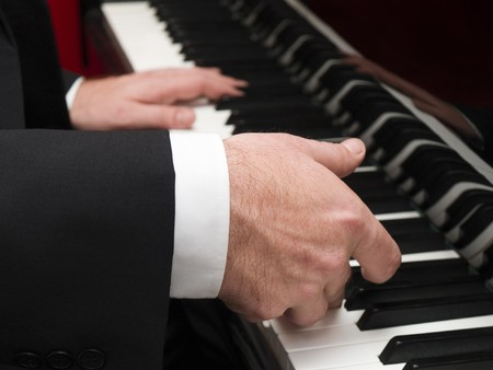 Stock photo of a closeup of a mans hands playing a piano.