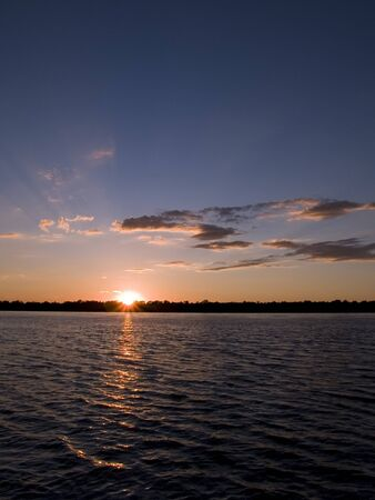 portrait orientation: Stock photo of a sunset over the Mississippi River