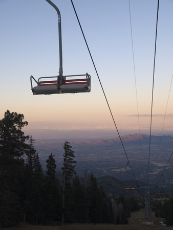 An empty ski lift framed against the sky at Sandia Peak, New Mexico in the fall.