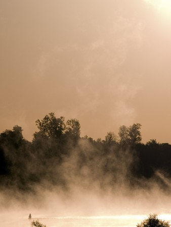 Fog rises high in the air over the Mississippi River just after sunrise. Фото со стока