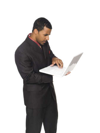 Isolated studio shot of an African American businessman looking at his laptop computer screen with a concerned expression. photo