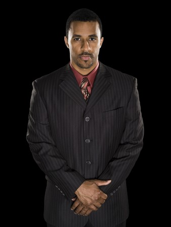 strong: Studio shot of a confident African American businessman with clasped hands looking intensely directly into the camera against a black background. Stock Photo