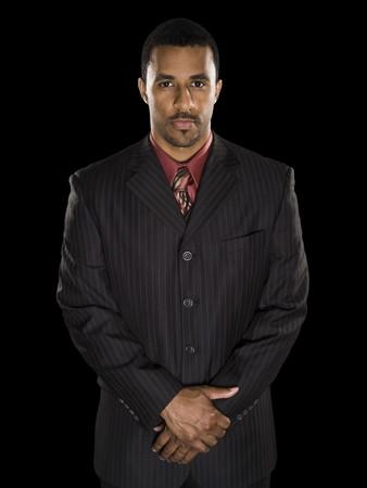 Studio shot van een zeker Afrikaans Amerikaans zakenman met geklemd handen op zoek intens rechtstreeks in de camera tegen een zwarte achtergrond. Stockfoto