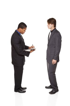 Isolated studio shot of two businessmen brainstorming and taking notes in a notebook. Imagens