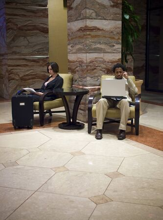 Hotel guests waiting in an upscale hotel lobby.