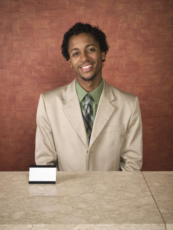 cheerfully: A hotel employee cheerfully welcomes guests. Stock Photo