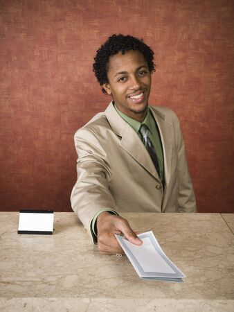 hotel worker: A hotel employee cheerfully welcomes guests. Stock Photo