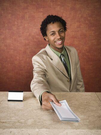 recepcionista: Un empleado del hotel alegremente recibe a sus hu�spedes.