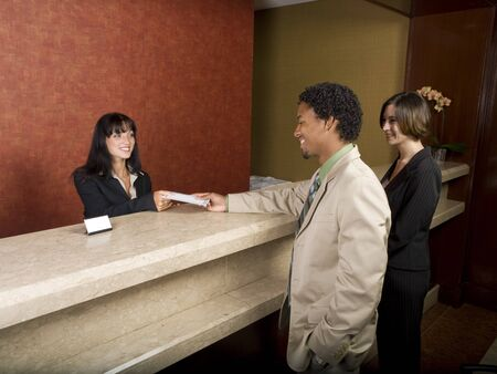 A hotel employee cheerfully welcomes guests. Stock Photo