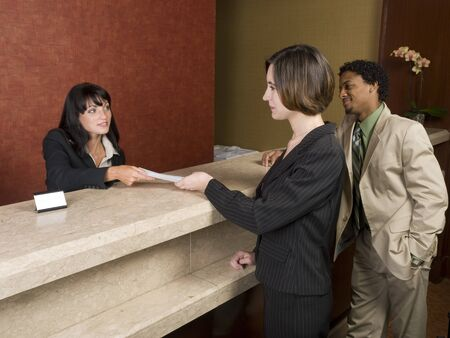 A hotel employee cheerfully welcomes guests. photo