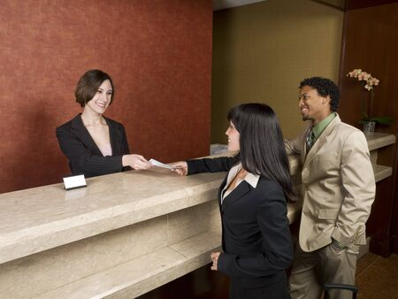 A hotel employee cheerfully welcomes guests. Banque d'images