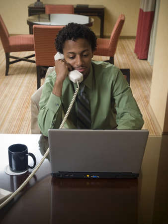 A businessman cheerfully reviews good results on his laptop computer in a hotel room during a business trip. photo