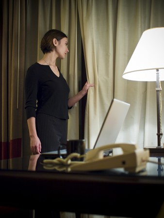 working woman: A businesswoman looks out a window thoughtfully while working late into the night in her hotel room while on a business trip.
