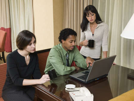 A team of businesspeople review results on a laptop while working late in a hotel room on a business trip. photo
