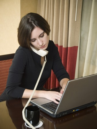 A businesswoman talks on the phone while working on her laptop computer in a hotel room during a business trip. photo
