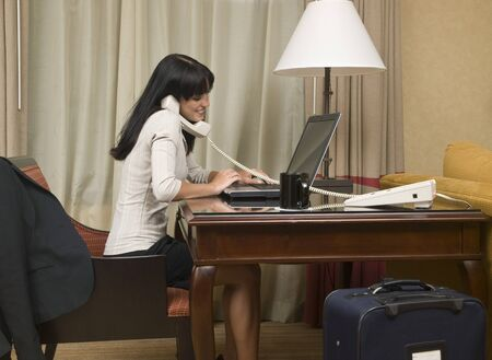 working on computer: A businesswoman cheerfully reviews good results on her laptop computer in a hotel room during a business trip. Stock Photo
