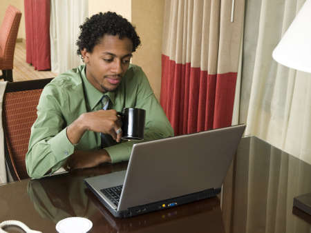 A business team cheerfully review good results on their laptop computer in a hotel room during a business trip. Stock Photo - 8081850
