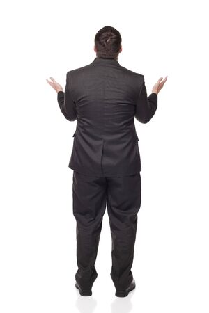Isolated full length studio shot of the rear view of an upset businessman raising his arms in disbelief as if giving up.