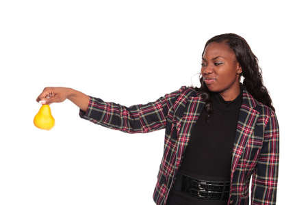 yuck: Isolated studio shot of an African American businesswoman holding a pear at arms length with a disgusted look on her face. Stock Photo