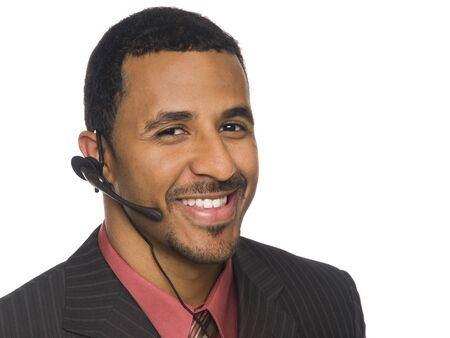 telephone headsets: Isloated closeup studio shot of an African American businessman smiling while talking on a telephone headset and looking at the camera.