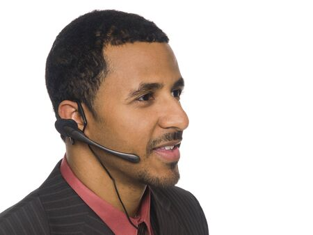 customer service representative: Isloated closeup studio shot of an African American businessman talking on a telephone headset. Stock Photo