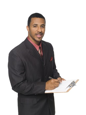 Isloated studio shot of an African American man looking at the camera while smiling and writing on a clipboard he is holding. Banque d'images