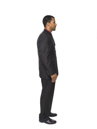 Isolated full length studio shot of a businessman facing to the right.