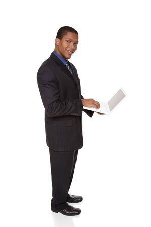 Isolated full length studio shot of a confident businessman looking at the camera while holding a laptop computer. Stock Photo - 8081505