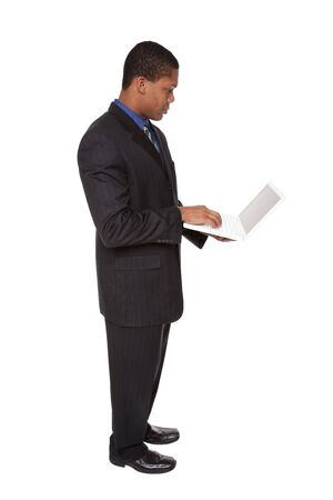 Isolated full length studio shot of a confident businessman looking at a laptop he is holding. Stock Photo - 8081538