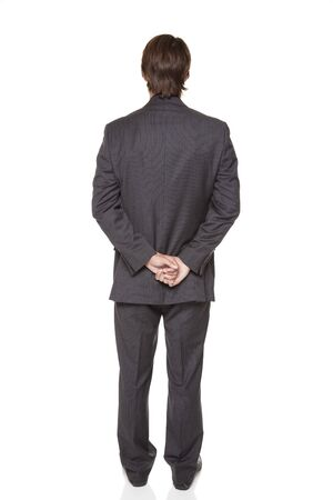 backside: Isolated full length studio shot of a businessman facing away from the camera with his hands clasped.