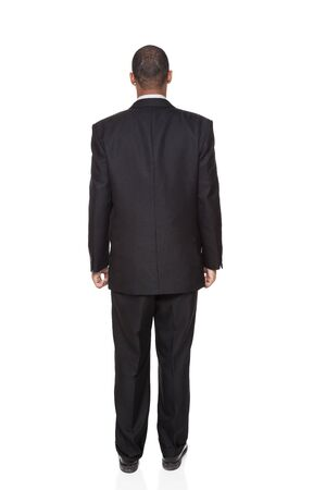 Isolated full length studio shot of the rear view of an African American businessman. photo