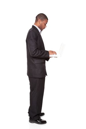 Isolated studio shot of an African American businessman standing and using a laptop computer. Stock Photo - 8081742