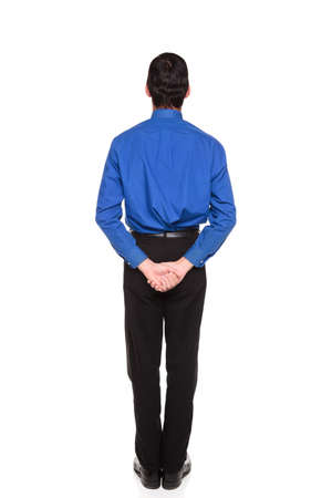 Isolated studio shot of a Caucasian businessman standing with his hands behind his back. Stock Photo - 8050882