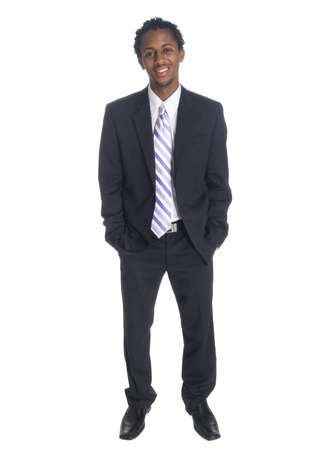 Isolated full length studio shot of a businessman smiling while looking at the camera with his hands in his pockets. Stock Photo