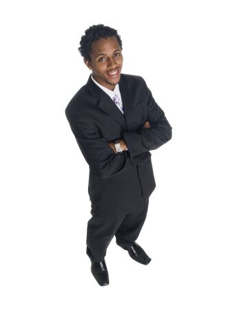 Isolated high angle studio shot of a businessman smiling at the camera with arms crossed. photo