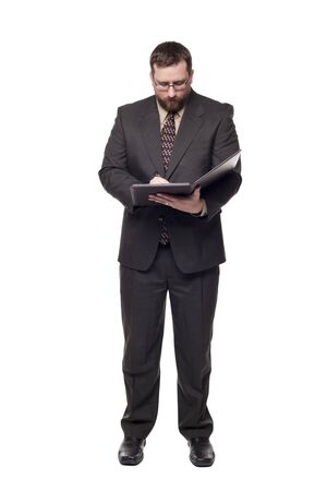 Isolated full length studio shot of the front view of a businessman writing on notepad.
