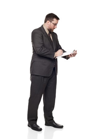 Isolated full length studio shot of the side view of a businessman writing on a clipboard. photo