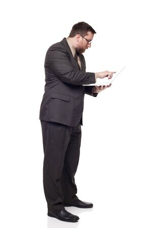 Isolated full length studio shot of the side view of a businessman working on a laptop he is holding while standing Stock Photo - 8081590