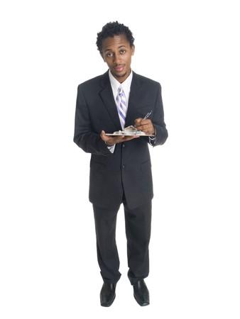 questionaire: Un pozo hab�a vestida de hombre de negocios estadounidense, escribiendo en un Portapapeles.  Foto de archivo