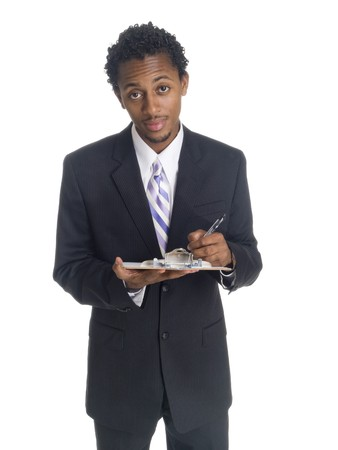 A well dressed African American businessman writing on a clipboard.