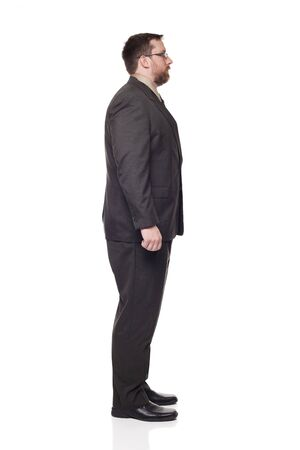 facing away: Isolated full length studio shot of the side view of a businessman in full suit looking away from the camera to the right.