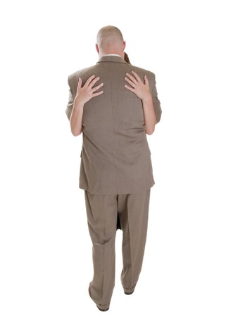 Stock photo of the back side of a well dressed businessman being embraced by a woman. Stock Photo