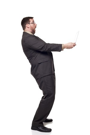 Isolated full length studio shot of the side view of a businessman holding a laptop at arms length as if afraid of what is coming out of the screen. photo
