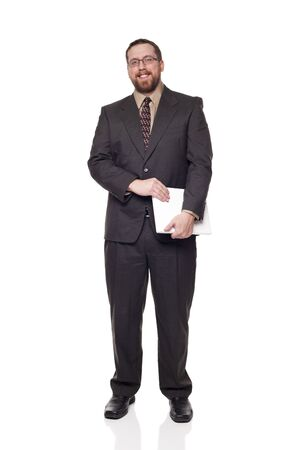 Isolated full length studio shot of the side view of a businessman carrying a laptop and looking at the camera. photo