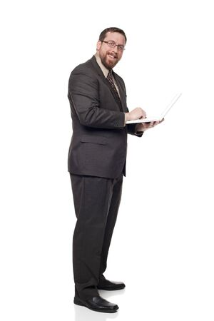 Isolated full length studio shot of the side view of a businessman working on a laptop he is holding while standing and looking at the camera. photo