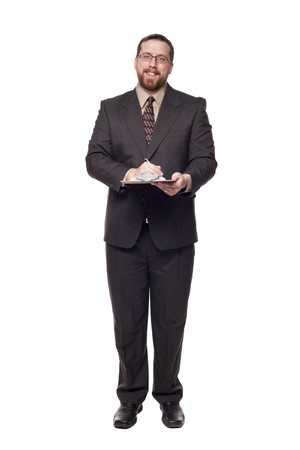 Isolated full length studio shot of the front view of a businessman smiling and looking at the camera while writing on a clipboard. photo