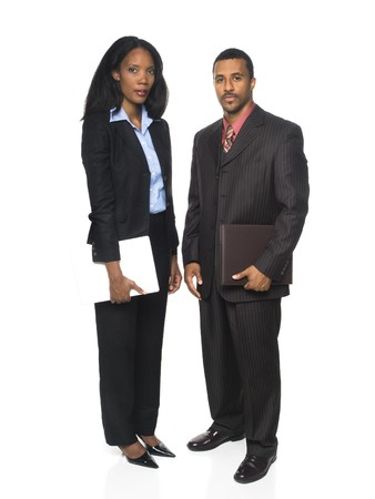 Isolated full length studio shot of a businesswoman and businessman looking at the camera and holding a computer and organizer. photo