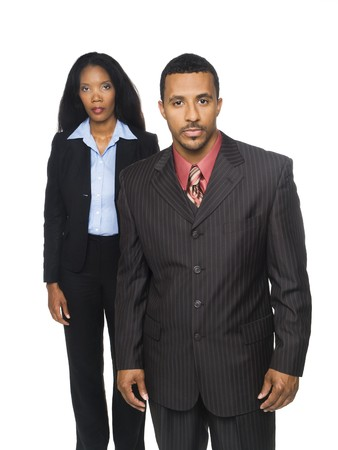 Isolated studio shot of a confident African American businessman and busineswoman looking at the camera against a white background.