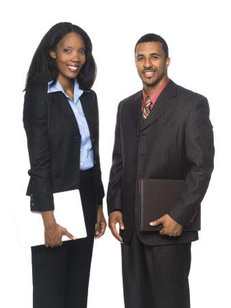 Isolated studio shot of a businesswoman and businessman smiling at the camera and holding a computer and organizer. photo