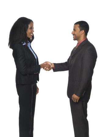 Isolated studio shot of a businesswoman and businessman happily shaking hands with each other in a warm greeting. photo